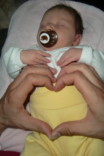 Peter bildar ett hjärta på sitt lilla hjärta.