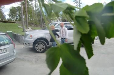 De hälsar på varandra innan de hoppar in i bilen. Båda ser glada och förväntansfulla ut.