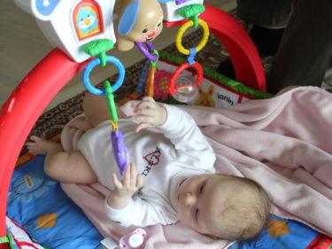 """Liv har fått ett """"Babygym"""". Hon älskar att ligga under det och försöka greppa och slå på leksakerna. Hon övar också på att vända sig, och det har hon faktiskt lyckats med två ggr. Hon gillar att ligga på mage och lyfta huvudet och spjärna med benen. Tänk att det går så fort."""