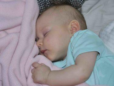 Min ljuva, goa bebis sover bredvid mig i sin säng och håller hårt om sin filt.