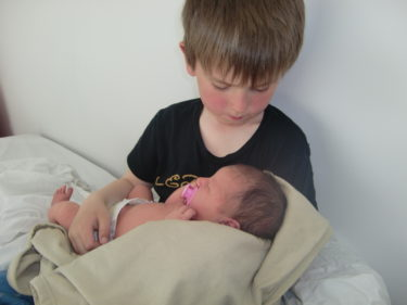 William med en nyfödd liten Livan i famnen.
