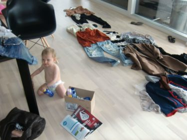 Liv kröp runt bland alla kläder och försökte få upp locket till sin solkräm. Tur att hon inte lyckades.