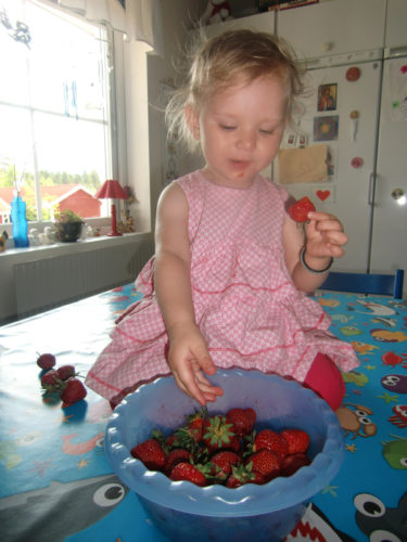 Liv trivdes på köksbordet med en stor skål jordgubbar.