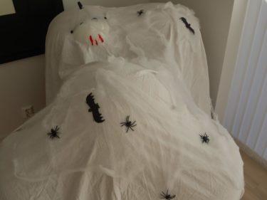 Täckte över vår fina randiga fåtölj med ett vitt lakan, spindelväv och spindlar.