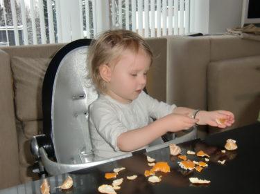 När hon skalat färdigt sin klementin delar hon upp den och äter klyfta för klyfta.