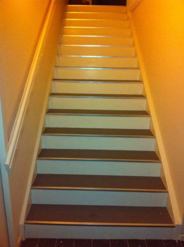 Trappen är vitmålad med grå trappsteg.