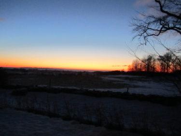 Se, vilken vacker utsikt. Solen går ner i horisonten och lämnar ett vackert sken på himlen.