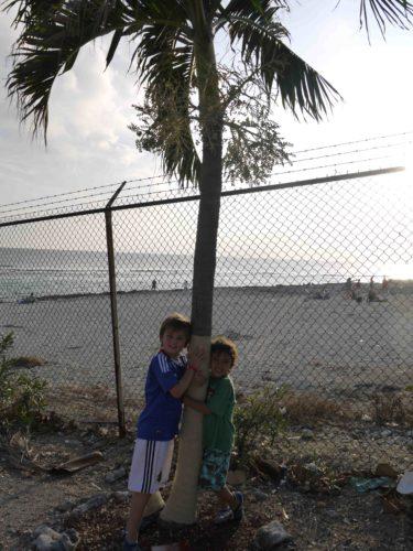 Mio lovade att ta en bild med en palm. Givetvis glömde de bort det så i sista sekund blev det en panikbild från en parkeringsplats på Cayman Island.