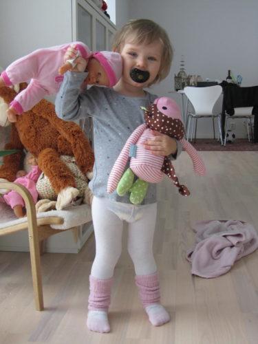 Hon älskar att sköta om sin docka, som hon kallar Babyen Mio. Hon matar. byter blöja och bäddar om den. Gulligt när hon leker mamma.