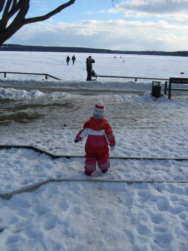 Liv traskar över den snötäckta minigolfbanan för att hinna ikapp pappa ut på isen.