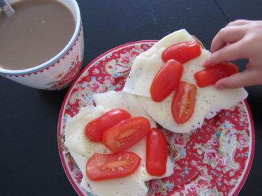 När jag tog en bild på min frukost dök en liten hand upp och stal en tomatskiva.