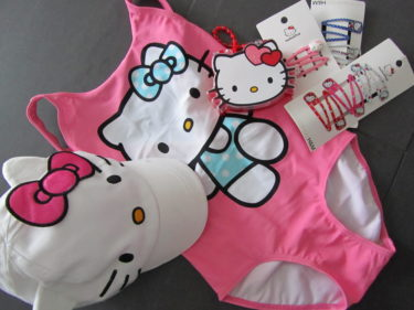 Hello Kitty baddräkt, keps, hårspännen och en liten väska.