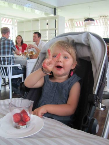 Liv visar dig att hon är två år. Hon fick jordgubbar till förrätt och satt bekvämt och högt i sin Joolz-vagn vid bordet och åt.